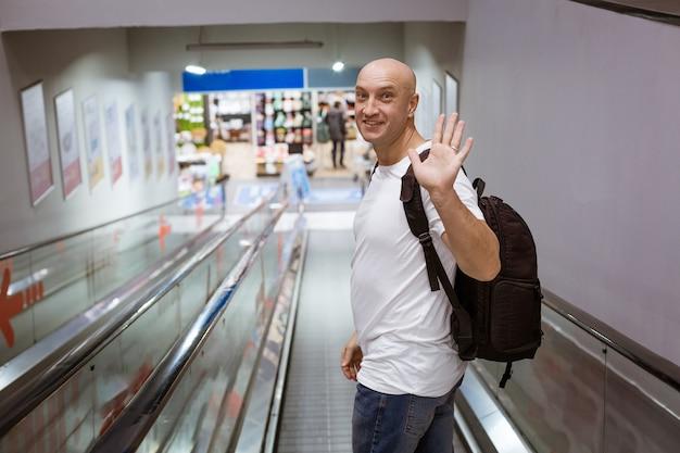 Glatzkopf geht mit einem rucksack die rolltreppe hinunter zum einkaufszentrum