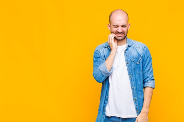 Glatzkopf hält wange und leidet unter schmerzhaften zahnschmerzen, fühlt sich krank, elend und unglücklich, sucht einen zahnarzt