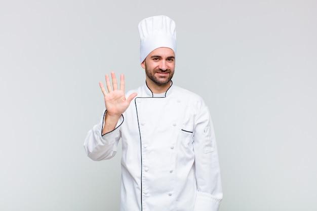 Glatzkopf lächelnd und freundlich aussehend, nummer fünf oder fünften mit der hand nach vorne zeigend, countdown