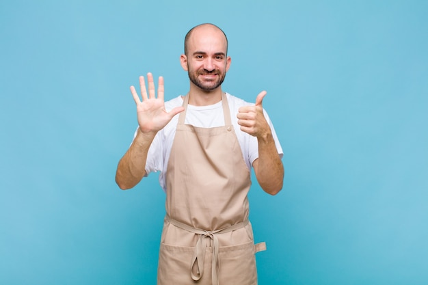 Glatzkopf lächelnd und freundlich aussehend, nummer sechs oder sechst mit der hand nach vorne zeigend, countdown