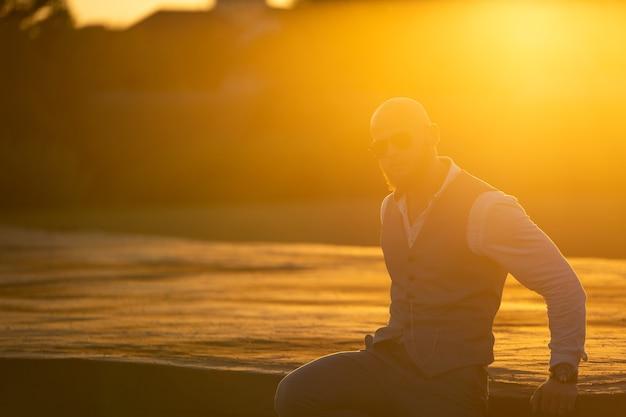 Glatzkopf mit stylischem bart und sonnenbrille auf verschwommenem stadthintergrund bei dramatischem sonnenuntergang. konzept von erfolg und wille