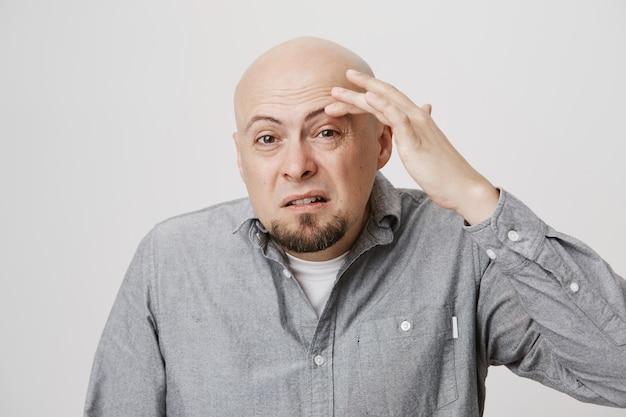 Glatzkopf mittleren alters, der augenbrauen berührt und blinzelt