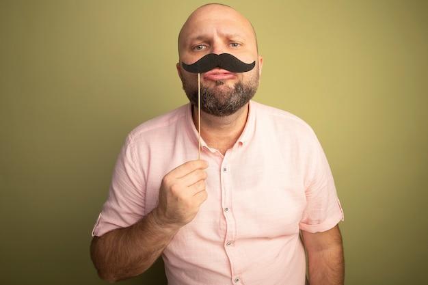 Glatzkopf mittleren alters, der geradeaus schaut und rosa t-shirt hält, das falschen schnurrbart auf stock hält, der auf olivgrün isoliert wird