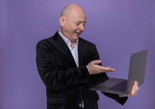 Glatzkopf mittleren alters im anzug, der laptop hält, der bildschirm mit skeptischem lächeln auf gesicht zeigt, das mit arm zeigt