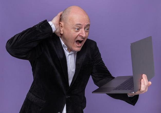Glatzkopf mittleren alters im anzug, der laptop hält, der bildschirm schreit, der verwirrt und aufgeregt ist, über lila wand stehend