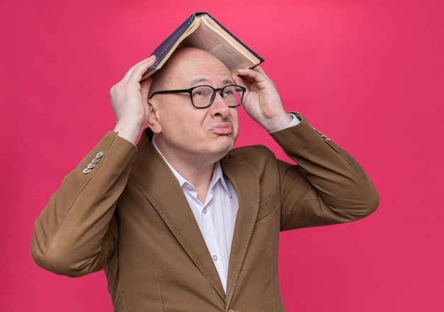 Glatzkopf mittleren alters im anzug mit brille, der ein buch über dem kopf hält und verwirrt aussieht