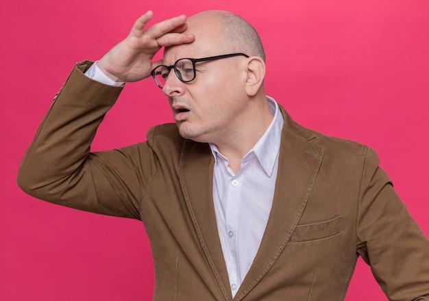 Glatzkopf mittleren alters im anzug mit brille, der mit der hand auf der stirn weit weg schaut