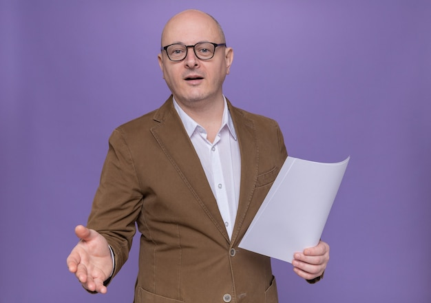Glatzkopf mittleren alters im anzug mit brille und leerer seite