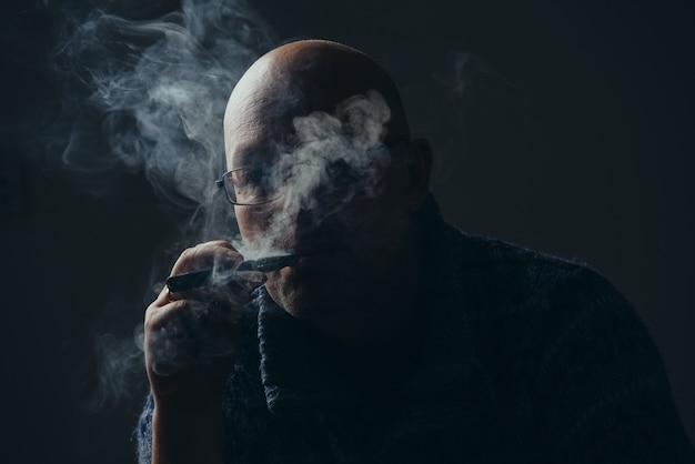 Glatzkopf raucht. zurückhaltend.