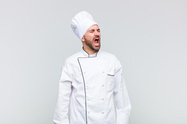Glatzkopf schreit wütend, schreit aggressiv, sieht gestresst und wütend aus