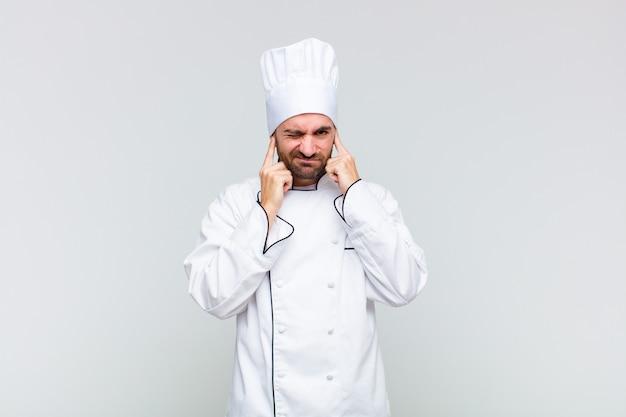 Glatzkopf sieht wütend, gestresst und genervt aus und bedeckt beide ohren mit einem ohrenbetäubenden geräusch, geräusch oder lauter musik