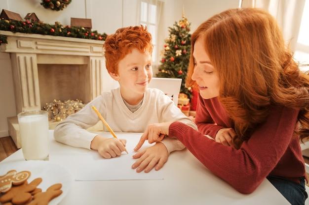 Glaubst du an wunder. liebevolle mutter, die sich ihrem kleinen sohn anschließt und ihm zu hause mit einem brief an den weihnachtsmann hilft.