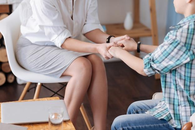 Glaubwürdigkeit verleihen. zwei personen, die auf den stühlen sitzen und armbänder am handgelenk haben, während sie festhalten