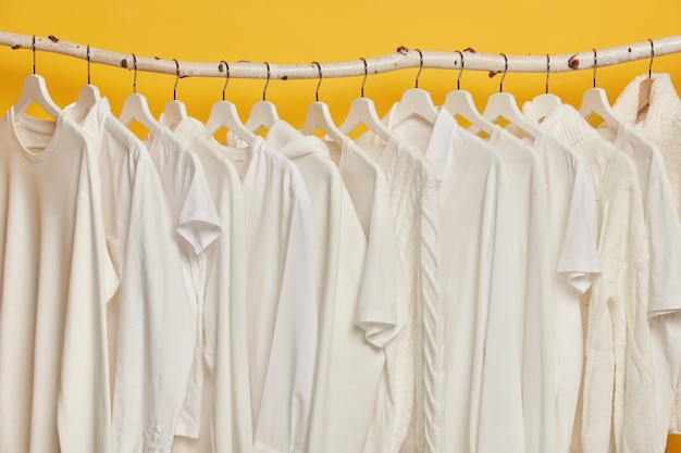 Gleiche weiße kleidung auf holzregalen im schrank. sammlung von kleidung auf kleiderbügeln, lokalisiert über gelbem hintergrund.