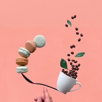 Gleichgewichtskonzept flach lag auf korallenpapierhintergrund, quadratische zusammensetzung. kreatives kaffeegetränkhintergrundbild mit kaffeebohnen und -blättern. balancierende tasse kaffee und macarons auf einem finger