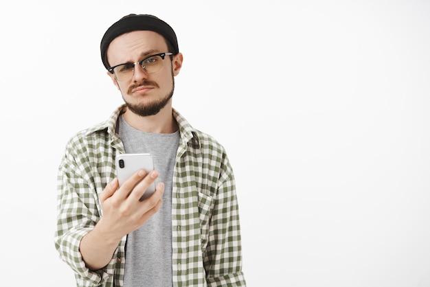 Gleichgültiger männlicher junger snob in brille und mütze mit bart hält smartphone grinsend und starrt nachlässig und unbeeindruckt, indem er ein angebot über nachrichten empfängt und unzufrieden ist