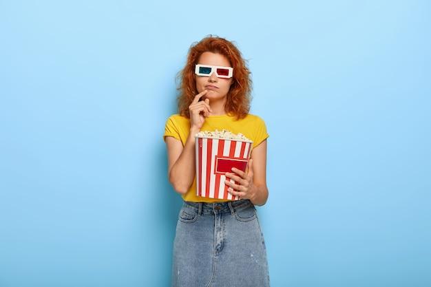 Gleichgültiges ingwer charmantes mädchen hält eimer mit popcorn
