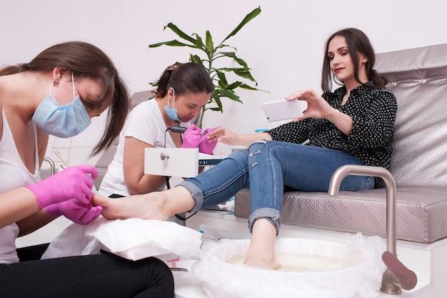 Gleichzeitiges gelpolitur-maniküre- und pediküre-selfie. professionelle körperpflege für schönheit und gesundheit im salon.