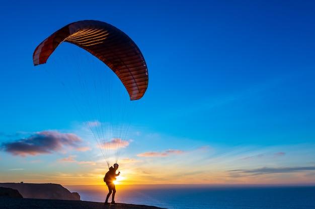Gleitschirm fliegt über diese küste bei sonnenuntergang. paragliding sport