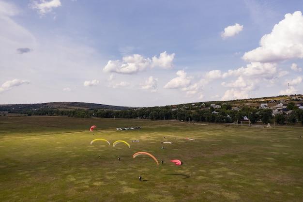 Gleitschirm silhouette fliegt über schöne grüne landschaft unter blauem himmel mit wolken.