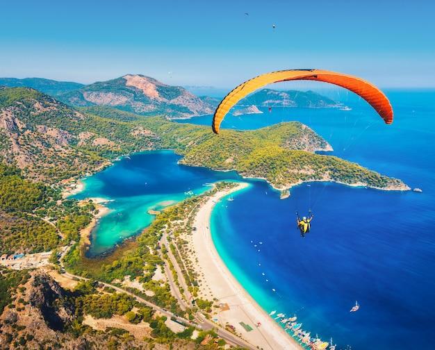 Gleitschirm-tandem, der über das meer mit blauem wasser und bergen an sonnigem tag fliegt