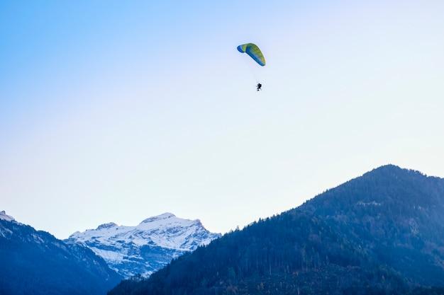 Gleitschirme, die mit paramotors mit schönem bergblick gegen blauen himmel fliegen