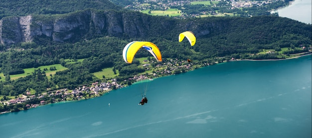 Gleitschirme mit dem parapente, das nahe vom see von annecy in den französischen alpen, in frankreich springt.