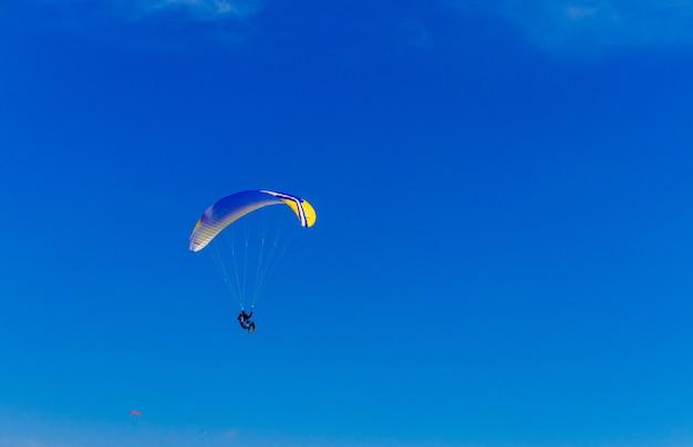 Gleitschirmfliegen am blauen himmel. fallschirm mit gleitschirm fliegt. extremsport, freiheitskonzept