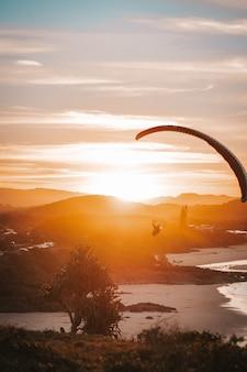 Gleitschirmfliegen am strand mit sonnenuntergang