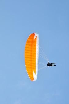 Gleitschirmfliegen auf einem blauen himmel