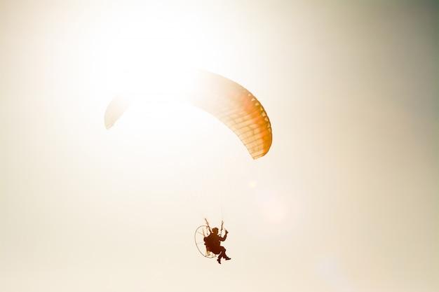 Gleitschirmfliegen mit motorschirm auf blauem himmel