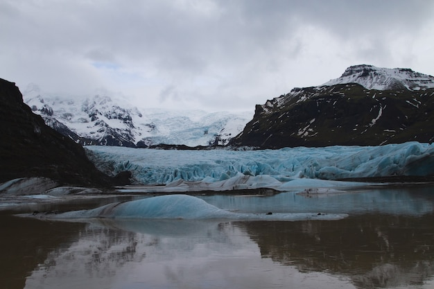 Gletscher umgeben von schneebedeckten hügeln, die über das wasser in island nachdenken