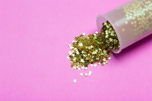Glitzer hintergrund. goldglittersterne verstreut auf einem farbigen hintergrund. urlaubskonzept
