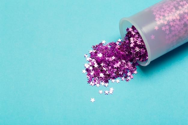 Glitzer hintergrund. lila glitzersterne verstreut auf einem farbigen hintergrund. urlaubskonzept