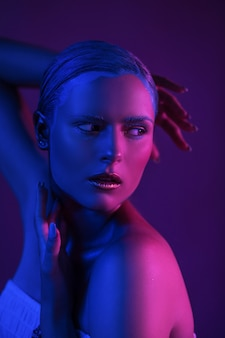 Glitzer-neonlichter auf der haut des sexy jungen modells im fotostudio