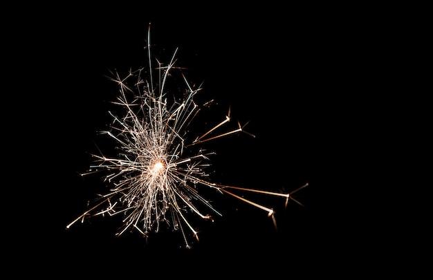 Glitzernde brennende wunderkerze im dunkeln. funken. weihnachten und neujahr. magisches licht