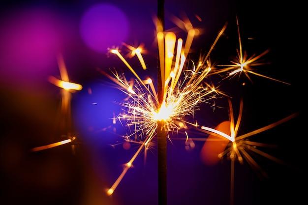 Glitzernde brennende wunderkerze mit lila und blauen lichtern