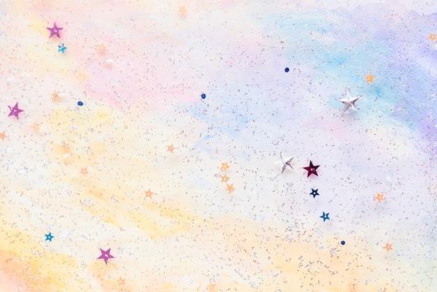 Glitzernde sternkonfetti auf buntem abstraktem pastellaquarellhintergrund