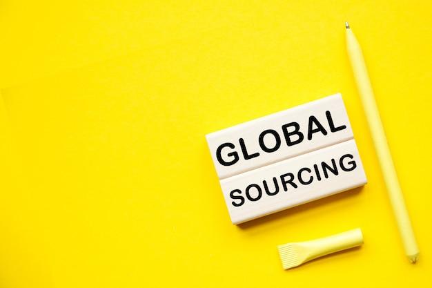 Global sourcing. holzstangen mit informationen auf dem desktop mit gelbem hintergrund.