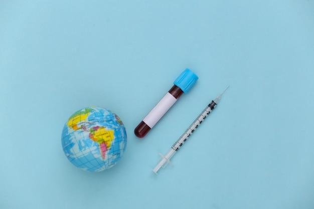 Globale bluttests covid-19. reagenzglas mit blut, spritze mit globus auf blauem hintergrund. ansicht von oben