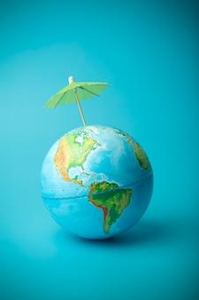 Globale erwärmung und klimawandel auf der erde konzept. erdkugel mit regenschirm. schutz der atmosphäre vor ultravioletter strahlung und ozonlöchern