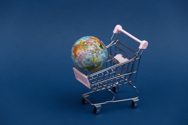 Globaler markt. mini-einkaufswagen mit globus auf klassischem blauem hintergrund