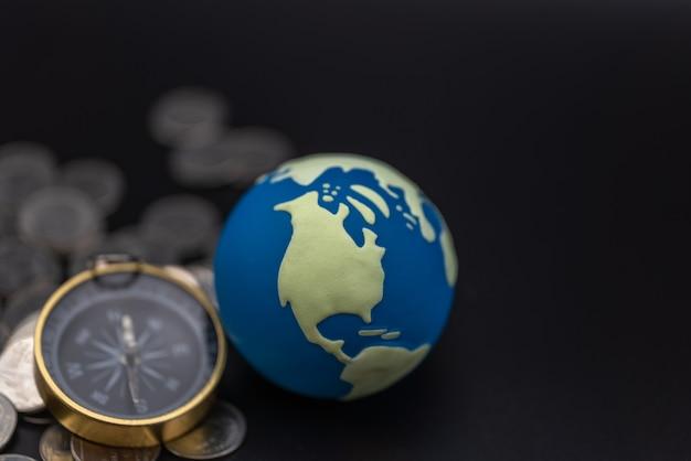 Globales geschäftsrichtungskonzept. nahaufnahme des mini-weltballs mit vintage-kompass und stapel von silbermünzen auf schwarzem hintergrund mit kopienraum.