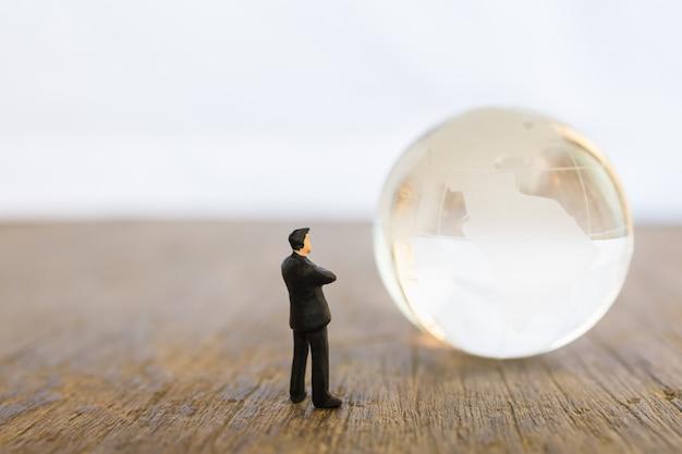 Globales und geschäftskonzept. geschäftsmannminileutezahl, die zur miniweltglaskugel auf holztisch mit kopienraum steht und schaut.