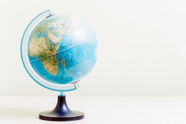 Globus auf dem hellen unscharfen hintergrund, nahaufnahme foto. touristisches konzept