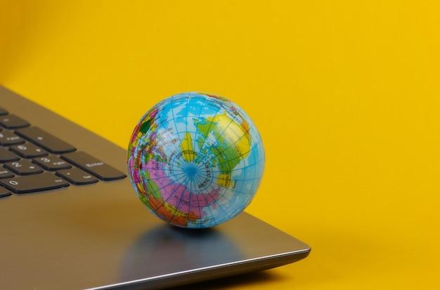 Globus auf einer laptoptastatur. world wide web, online. gelber hintergrund