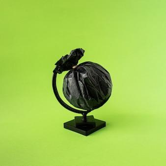Globus aus schwarzem müllsack. planetenerde aus kunststoff. grüner hintergrund. minimales konzept.