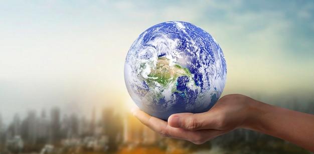 Globus, erde in menschlicher hand, hält unseren planeten glühend.