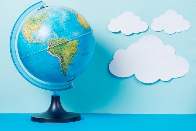 Globus in der nähe von papier wolken
