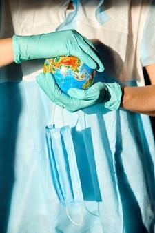 Globus in einer medizinischen maske in den händen des arztes in hartem licht